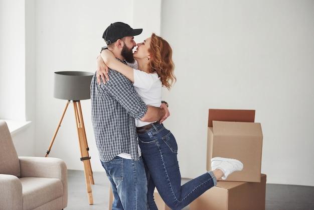 Stoel en dozen bij hen in de buurt. gelukkig paar samen in hun nieuwe huis. conceptie van verhuizen