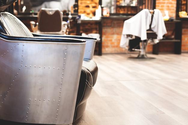 Stoel om je haar te wassen in een kapperszaak. barbershop interieur. brute plaats. lederen fauteuil met metalen bekleding. selectieve aandacht.