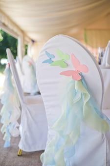 Stoel versierd met vlinders gemaakt van papier.