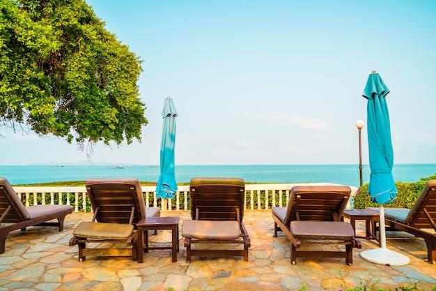 Stoel zwembad en parasol rond zwembad met kokospalm - vakantie en vakantie concept
