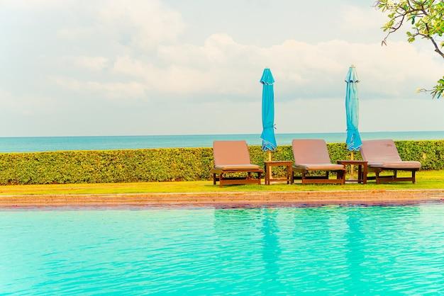 Stoel zwembad en parasol rond zwembad met oceaan zee achtergrond