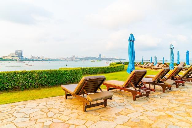Stoel zwembad of bed zwembad en parasol rond zwembad met uitzicht op zee strand in pattaya in thailand