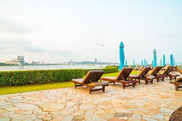 Stoel zwembad of bed zwembad en parasol rond zwembad met zee strand in pattaya in thailand