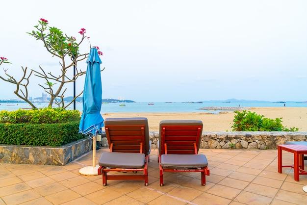 Stoel zwembad of bed zwembad en parasol rond zwembad met zee strand