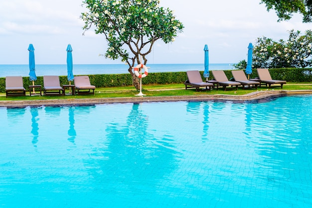 Stoel zwembad of bed zwembad met parasol rond zwembad