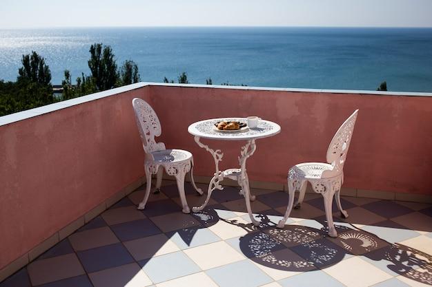 Stoelen en een tafel bevinden zich op het balkon met prachtig uitzicht op zee