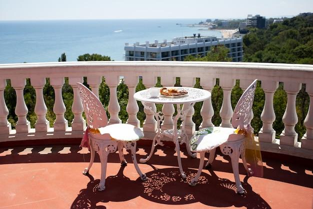 Stoelen en een tafel staan op de veranda met prachtig uitzicht op zee