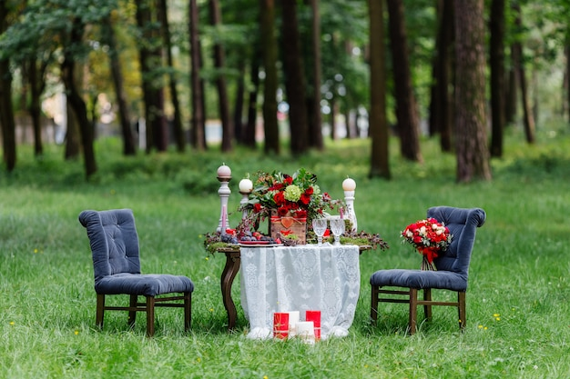 Stoelen en kaarsen, bloemen, keramische schalen met fruit, staande op het kanten tafelkleed en mos