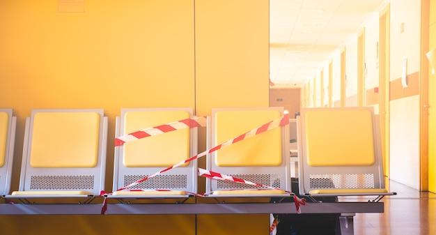 Stoelen in de wachtkamer van een openbaar ziekenhuis met aanwijzingen om sociale afstand te bewaren en besmetting met het coronavirus te voorkomen.