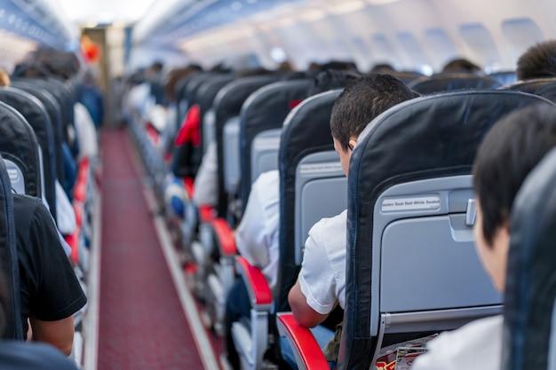 Stoelen in het vliegtuig en passagiers zitten in het hele gebied te wachten op het vliegtuig dat opstijgt vanaf de startbaan.