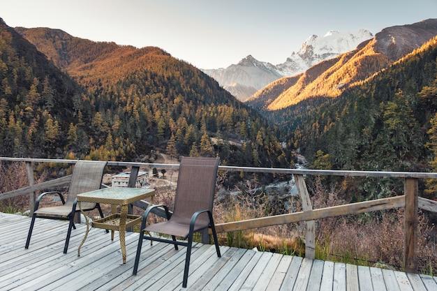 Stoelen met tafel op houten balkon met vallei in de herfst in de avond