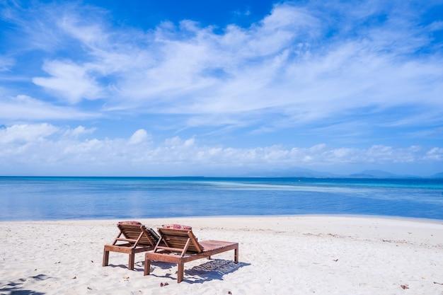Stoelen op het verbazingwekkende mooie zandstrand vlakbij de oceaan met blauwe lucht.