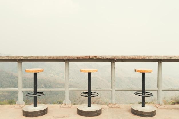 Stoelen op zonnig terras met uitzicht op de baai en decoratie in moderne woning.