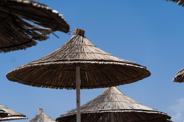 Stoelen paraplu in palm beach tropische vakantie banner. strand met palmbomen en hemel. zomervakantie reizen vakantie achtergrond concept. tropisch landschap. bergen. ansichtkaart.