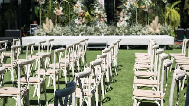 Stoelen versierd met bloemen in openlucht huwelijksceremonie in de tuin.
