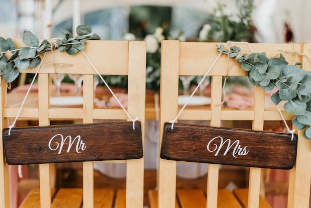 Stoelen voor bruid en bruidegom versierd met bloemen met borden de heer en mevrouw voor huwelijksceremonie