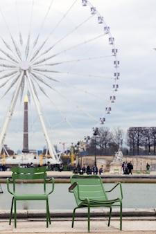 Stoelen voor rust op de achtergrond van het grote wiel op de place de la concorde in parijs. frankrijk