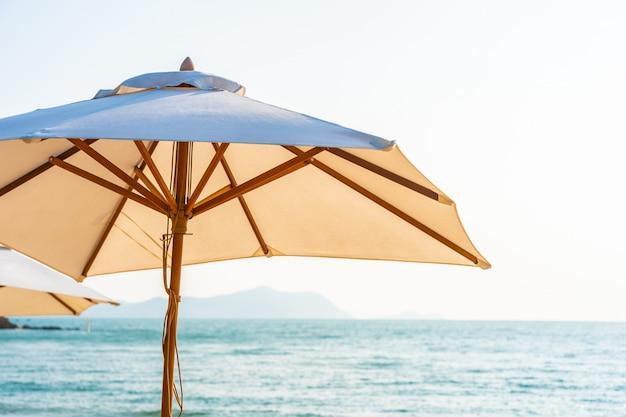 Stoelparaplu en zitkamer op de mooie strand overzeese oceaan op hemel