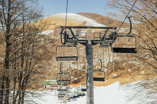 Stoeltjeslift, besneeuwde skipiste in bergen en blauwe lucht in de winter.