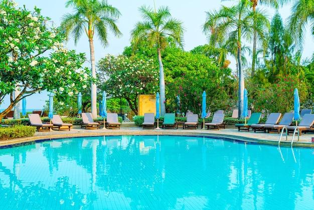Stoelzwembad en parasol rond zwembad met kokospalm - vakantie- en vakantieconcept