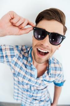 Stoer en trendy. bovenaanzicht van vrolijke jonge man die brillen aanpast