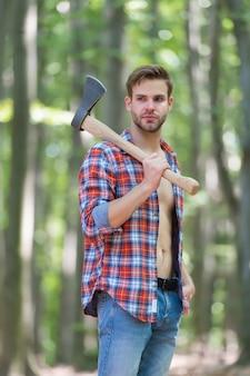 Stoere look ongeschoren man draagt bijl in het bos houthakkerstijl axeman draagt een open geruit overhemd