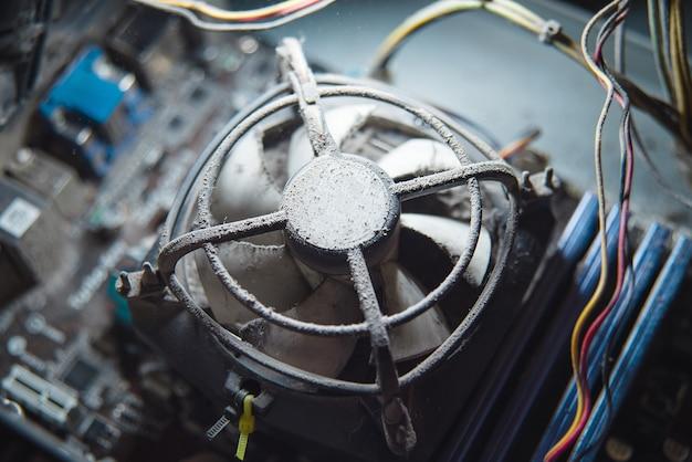 Stof op computer pc-processorkoeler met moederbord en fragment van computerbehuizing