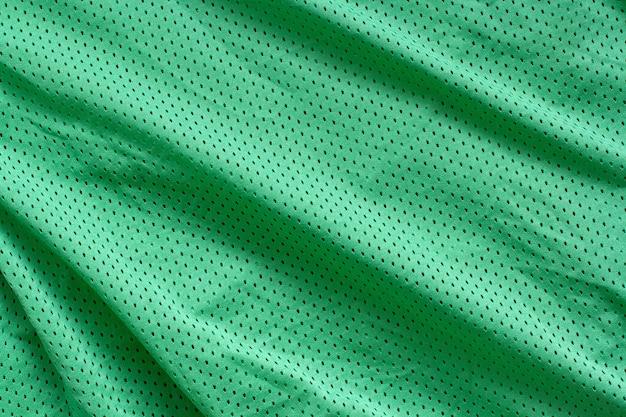 Stof textuur. groene stof met plooien. ruwheden en golven op het oppervlak.