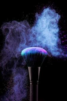 Stof van poeder en make-upborstel op zwarte achtergrond