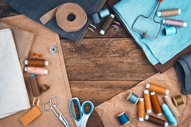 Stoffen, draden en schaar met een lint op een natuurlijke houten achtergrond.