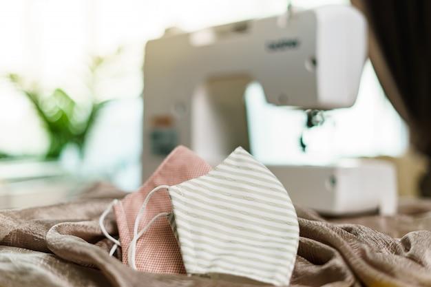 Stoffen en naaimachine voor het naaien van een antivirus gezichtsmasker tijdens de coronavirus pandemie