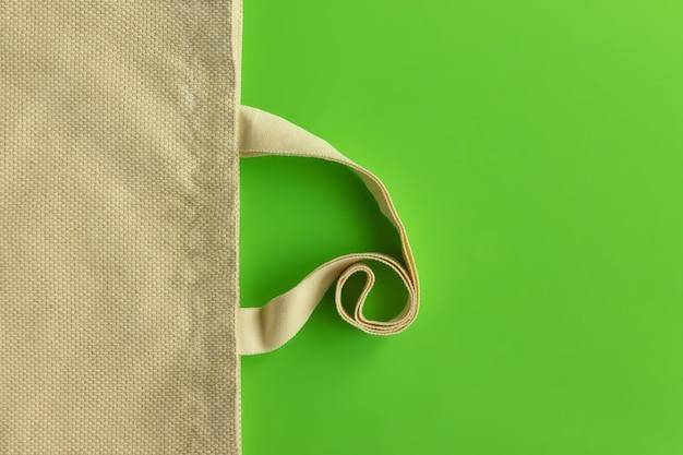 Stoffen katoenen boodschappentas op een groene achtergrond. nul afval en ecologisch concept. bovenaanzicht. ruimte kopiëren.