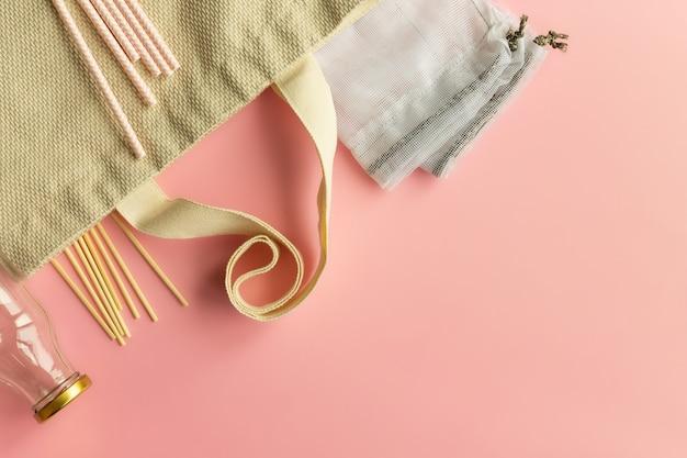 Stoffen katoenen boodschappentassen, glazen flessen, papieren rietjes en houten stokjes op een roze achtergrond. bovenaanzicht. ruimte kopiëren.