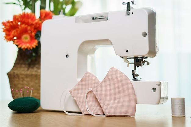 Stoffen, naai-accessoires en naaimachine voor het naaien van een antivirus gezichtsmasker tijdens de coronavirus pandemie.