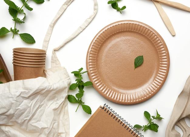 Stoffen tas en wegwerpservies van bruin kraftpapier, groene muntblaadjes