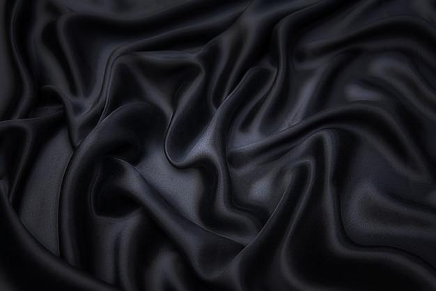 Stoffentextuur, achtergrond voor ontwerp. textuur van zwarte zijde of katoen of wollen stof. mooi patroon van golvende stof.