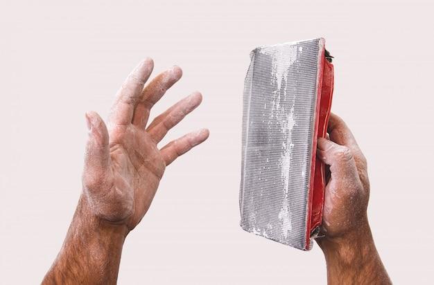 Stoffige handen van een arbeider en een hulpmiddel om stopverf te malen.
