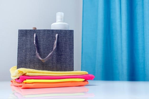 Stofverfrisser spray, wasverzachter in een papieren zak op stapel schoon, gestreken gekleurd wasgoed. textiel en kleding zorgconcept.