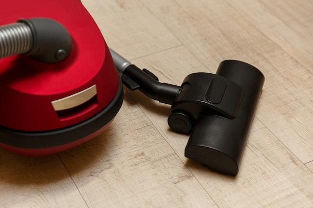 Stofzuiger op de vloer, schoonmaakdienst, nieuwe rode stofzuiger.