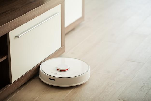 Stofzuigerrobot draait op houten vloer in een woonkamer