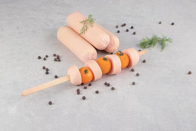 Stok van gesneden worstjes met tomaten op marmeren achtergrond.