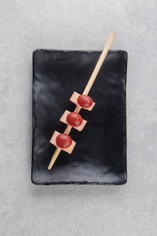 Stok van worstjes met ketchup op zwarte plaat.