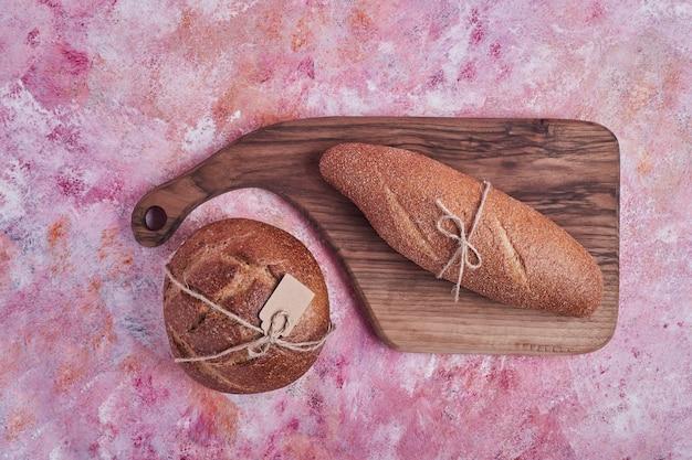 Stokbrood en broodjes op een houten bord.