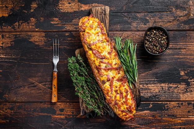 Stokbrood gevuld met ham, spek, groenten en kaas op een houten bord. donkere houten achtergrond. bovenaanzicht.