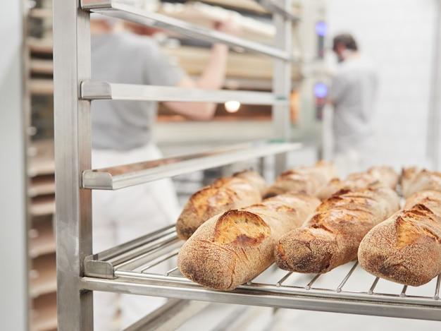 Stokbrood van brood op een rekkarretje interieur van een bakkerijarbeiders op de achtergrond onscherp