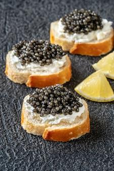 Stokbroodplakken met roomkaas en zwarte kaviaar
