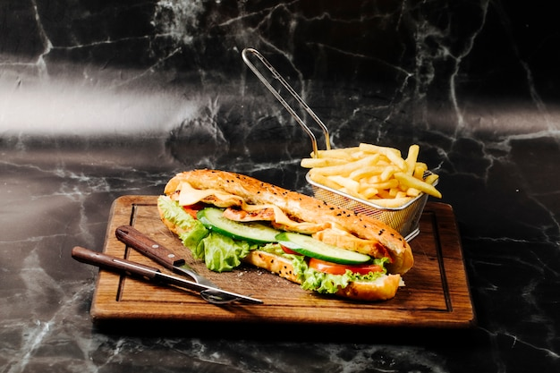 Stokbroodsandwich met gemengde ingrediënten en frieten op een houten raad.