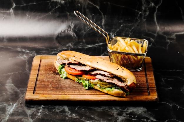 Stokbroodsandwich met gemengde ingrediënten en frieten.
