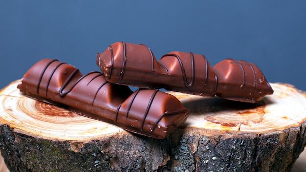 Stokken van heerlijke snoepjes met melkchocola op een houten tribune op een grijze close-up als achtergrond.