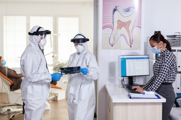 Stomatologie-assistent die een pb-pak met gezichtsafscherming draagt